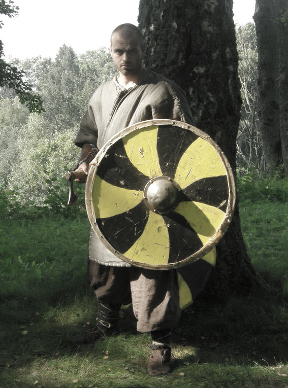 Bojovník je chráněn kroužkovou zbrojí, na hlavě má jednu z variant přilby nalezené v Gjermundbu s brýlemi chránícími oči a kroužkovým závěsem. Ruce mu chrání nátepníky s kovovými pásky a rukavice. Vyzbrojen je mečem a dlouhou sekerou – danaxem. Podle výzbroje jde zřejmě o hersira nebo jarla.